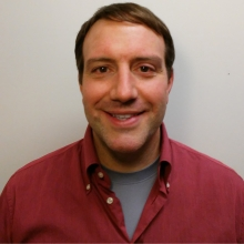 Faculty profile image of Dr. Aaron A. Toscano with red shirt